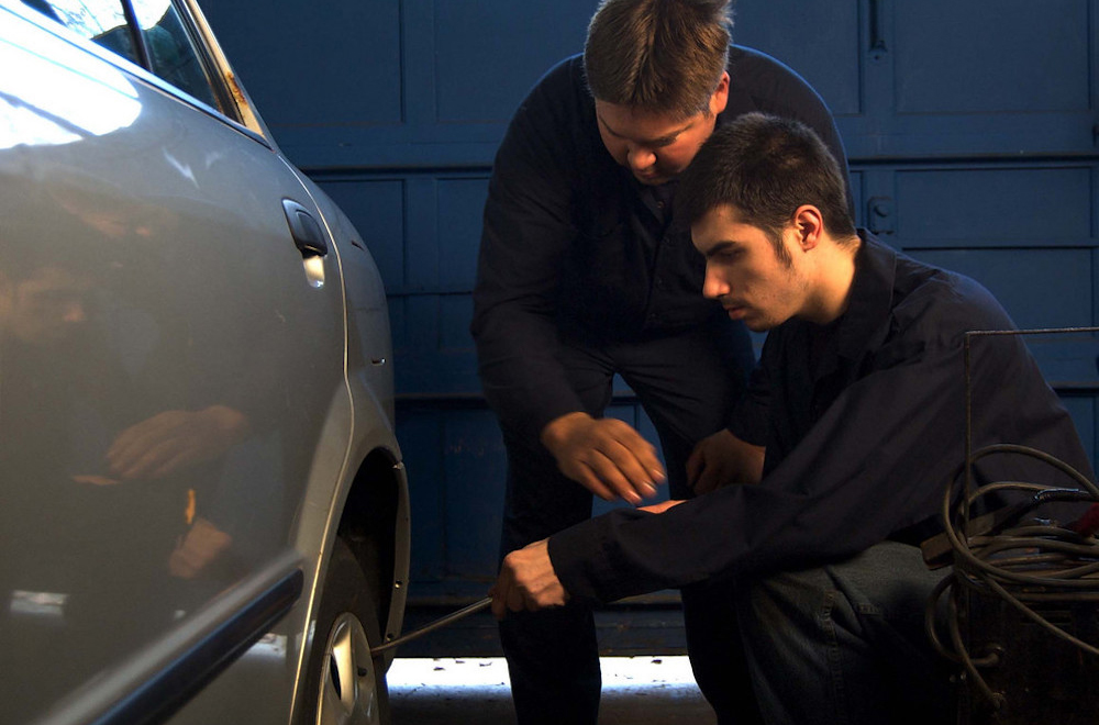 Two people working together to change a car tire